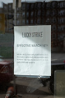 A sign on the door of the temporarily closed Lucky Strike, part of a bowling alley chain with bars and restaurants inside, located across Lansdowne Street from Fenway Park, is seen here in Boston, Massachusetts, on Wed., Jan. 6, 2021. The sign announces that the business closed since March 16, 2020.