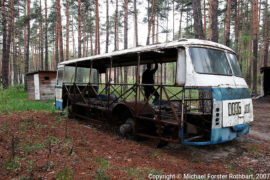 On April 26,1986, an explosion at Ukraine's Chernobyl Nuclear Power Plant changed history, sending radiation and political shockwaves across Europe. Nearby towns and villages were first evacuated, then abandoned. Vehicles used for evacuation and decontamination became too radioactive to keep. This abandoned bus, stripped of parts, rusts away in the forest near Lyutezh, Ukraine.  <br /> ------------------- <br /> This photograph is part of Michael Forster Rothbart's After Chernobyl documentary photography project.<br /> © Michael Forster Rothbart 2007-2010.<br /> www.afterchernobyl.com<br /> www.mfrphoto.com <br /> 607-267-4893 o 607-432-5984<br /> 5 Draper St, Oneonta, NY 13820<br /> 86 Three Mile Pond Rd, Vassalboro, ME 04989<br /> info@mfrphoto.com<br /> Photo by: Michael Forster Rothbart<br /> Date:  5/2007    File#:  Canon 20D digital camera frame 6582<br /> ------------------- <br /> Original caption: .Photo title:.Abandoned bus in Lyutezh..Caption:.Many vehicles used for evacuation and decontamination were too radioactive to keep using after the Chernobyl accident. Trucks, busses and contaminated equipment were buried in over 800 dumpsites, mostly unmarked. Other machinery was simply abandoned. These have since been stripped of any salable parts by scrap metal dealers...Outside the restricted Exclusion Zone are 2,293 small villages in Ukraine where the land was slightly contaminated by radioactive fallout. Those who still live here receive very little information about possible health risks. Many receive small government pensions for their status as Chernobyl survivors...Quote: none.-------------------
