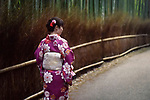Japanese woman in a purple kimino walking through Arashiyama bamboo forest in Kyoto, Japan. Image © MaximImages, License at https://www.maximimages.com