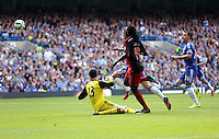 Pictured: Bafetimbi Gomis of Swansea (C) shoots wide against Thibaut Courtois (C) chased by Gary Cahill of Chelsea. Saturday 13 September 2014<br /> Re: Premier League Chelsea FC v Swansea City FC at Stamford Bridge, London, UK.