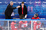 Sochi, RUSSIA - Mar 13 2014 - Assistant Coach Curtis Hunt and Head Coach Mike Mondin talk to the players as Canada takes on USA in Sledge Hockey Semi-Final at the 2014 Paralympic Winter Games in Sochi, Russia.  (Photo: Matthew Murnaghan/Canadian Paralympic Committee)