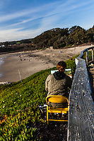 A young man sits on a yellow metal chair working intently on a canvas propped on his portable artist easel at Natural Bridges State Park in Santa Cruz, California.