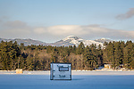 Ice fishing on snow-covered Kezar Lake under the White Mountain National Forest in Center Lovell, ME