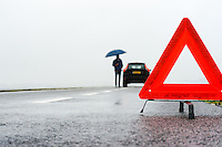 man with an umbrella besides his broken car alongside a road in the middle of nowhere