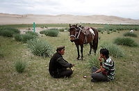 Local Tibetan men near to sands dunes next to Qinghai Lake. Qinghai Lake, China's largest inland body of water lies at over 3000m on the Qinghai-Tibetan Plateau. The lake has been shrinking in recent decades, as a result of increased water-usage for local agriculture. Qinghai Province. China. 2010