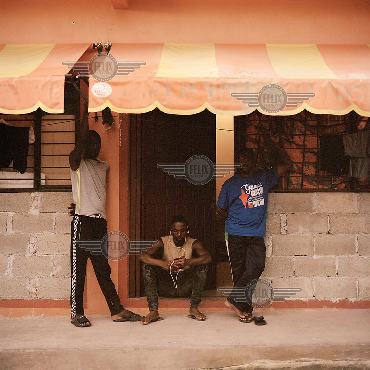 Gutbre Germain (32, sitting), a migrant from Burkina Faso, checks his phone while sitting in the doorway of the tiny single-bedroom apartment he lives in with 14 other African nationals who are all awaiting for a resolution of their migratory process. Gutbre lived in Brazil for four years but left when the economic situation worsened and started a three month journey to reach Mexico by land. They are just some of hundreds of migrants waiting for the Mexican authorities to allow them to continue with their journey north which stalled after Mexico stopped issuing transit visas following pressure from the US government.