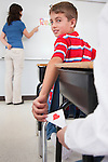 USA, Illinois, Metamora, Girl and boy passing love letter in class, female teacher at whiteboard in background