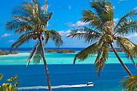 Palm trees and boat over turquoise water lagoon of Bora Bora island, romantic honeymoon destination, near Tahiti, French Polynesia, Pacific Ocean