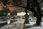 A couple strolling toward the White House on a snowy winter night in Lafayette Park.  Lafayette Park is known as Presidents Park in Washington, D.C. encompasses the White House, a visitor center, Lafayette Park. and The Ellipse. Presidents Park was the original name of Lafayette Park and Square..