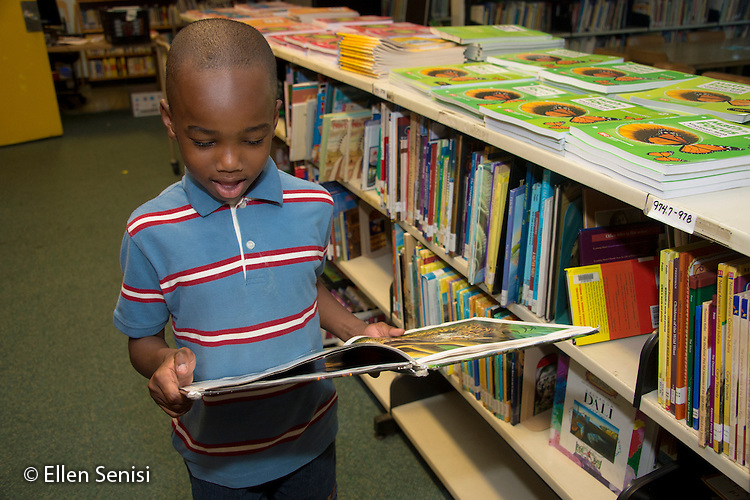 MR / Schenectady, NY. Zoller Elementary School (urban public school). Kindergarten classroom. Boy (5) looks at book in school library. MR: Abd2. ID: AM-gKw. © Ellen B. Senisi.