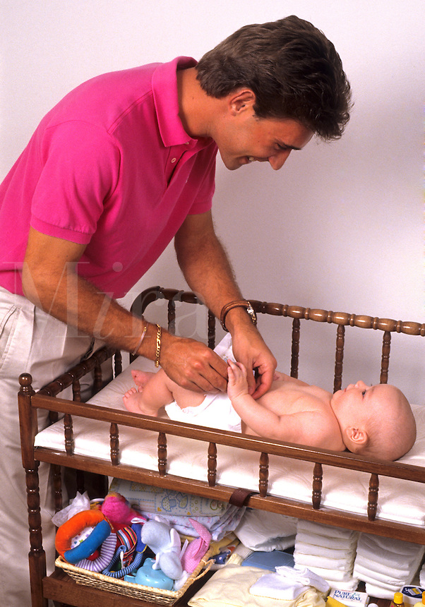 Father enjoying fatherhood changing infants diaper on changing table at home