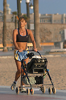 The coast walk. A woman in tank top and shorts walking a child in a pram stroller. Sitges, Catalonia, Spain