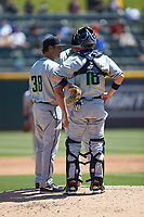 Gwinnett Stripers pitching coach Reid Cornelius (38) has a meeting on the mound with catcher Chris Stewart (18) and starting pitcher Luiz Gohara (52) during the game against the Charlotte Knights at BB&T BallPark on May 2, 2018 in Charlotte, North Carolina.  The Knights defeated the Stripers 6-5.  (Brian Westerholt/Four Seam Images)