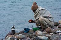 India, Rishikesh.  Worshipper Preparing an Offering for the River Ganges (Ganga).