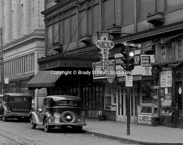 Pittsburgh PA:  View of stores along Diamond Street near the corner of Wood Street.  Nearby stores include; Diamond Key Store, Diamond Market, John M Roberts and Sons, Hendel Building, and Diamond Pawn Shop