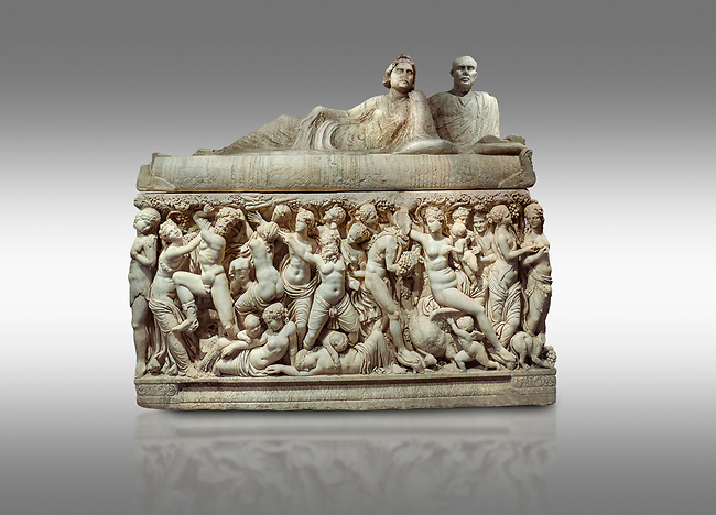 """Roman relief sculpted sarcophagus depicting a scene with Dionysus made in a Greek Attica workshop, 3rd century AD, Perge Inv 1.35.99. Antalya Archaeology Museum, Turkey.<br /> <br /> The lid of the sarcophagus is sculpted into the form of a """"Kline"""" style Roman couch on which lie Julianus &  Philiska. This type of Sarcophagus is also known as a Sydemara Type of Tomb.. Against a grey background."""