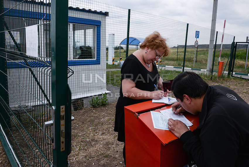People filling expatriation documents as they  cross the Ukrainian-Russian border at Izvarine check point - one of border crossings controlled by Luhansk Peoples Republic. According to rebels around 5 thousand people leave Ukraine every day through Izvarine border crossing.