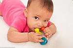 5 month old baby girl on stomach closeup holding toy mouthing or biting it