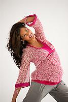 Pregnant Hispanic woman, kneeling, hands in her hair