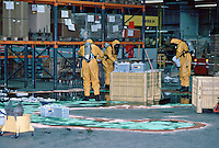 Firefighters wearing breathing apparatus and chemical protection suits attending a chemical spillage in a large factory. They are using an absorbent powder to soak up the chemical. This image may only be used to portray the subject in a positive manner..©shoutpictures.com..john@shoutpictures.com.