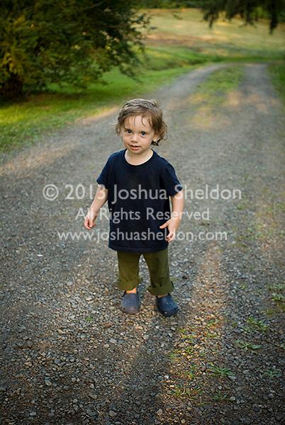 Baby boy standing, looking at camera