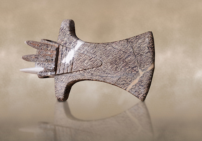 Hittite ceremonial stone cult axe head. Hittite Period 1650 - 1450 BC, Ortakoy Sapinuva . Çorum Archaeological Museum, Corum, Turkey. Against a warm art bacground.