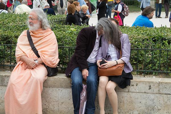 Lovers kissing and Hindu pundit, Paris, France.