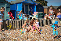 """A young woman breastfeeding her baby while sunbathing on the beach with a friend, and talking to their older children.<br /> <br /> Image from the breastfeeding collection of the """"We Do It In Public"""" documentary photography picture library project: <br />  www.breastfeedinginpublic.co.uk<br /> <br /> <br /> Hampshire, England, UK<br /> 03 /09/2013<br /> <br /> © Paul Carter / wdiip.co.uk"""