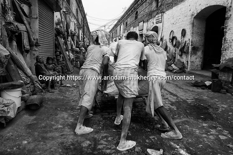 Laborers push a over loaded cart at Burrabazzar in Kolkata, India.