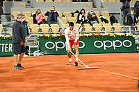 3rd October 2020, Roland Garros, Paris, France; French Open tennis, Roland Garros 2020;  The court is worked on by groundskeepers after the rain during the Djokovic versus Galan match and Djokovic lends a hand