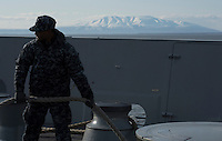 """130506-N-DR144-925 ANCHORAGE, Alaska (May 6, 2013)- Seaman Ross Daquavion stows morning lines on the foc'sle as San Antonio-class amphibious transport dock ship USS Anchorage (LPD 23) passes Mt. Susitna, known locally as """"Sleeping Lady,"""" while leaving the Port of Anchorage. Anchorage departed its namesake city of Anchorage, Alaska after a five-day port visit for the ship's commissioning. (U.S. Navy photo by Mass Communication Specialist 1st Class James R. Evans / RELEASED)"""