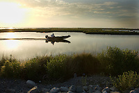 A motorised skiff navigates parallel to the Isle Jean Charles access road. The open water here was once marsh land solid enough to walk on. Trappers once used this land to hunt. In many places along the southeast coast of Louisiana, water is replacing solid land as coastal erosion carries soil out to sea.
