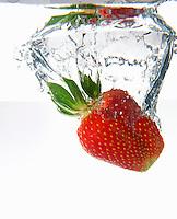 One strawberry fruit splashing underwater, white background, studio