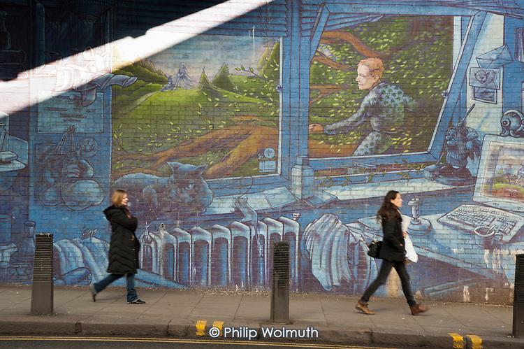 Pedestrians walk past a mural in Kilburn, London.
