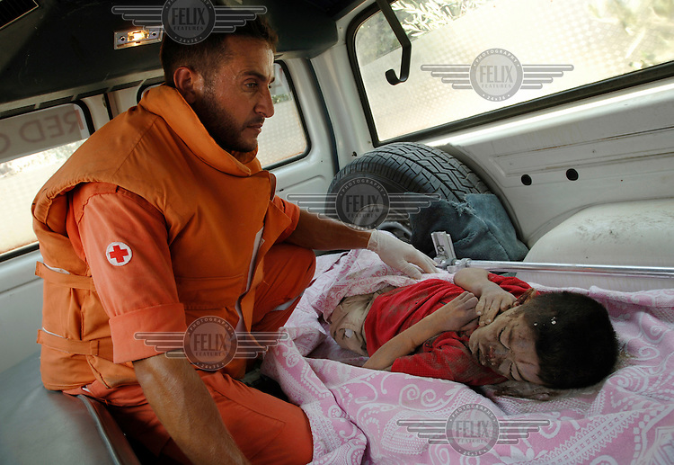 A Lebanese Red Cross rescue worker with a dead boy of about nine years old whose body had been retrieved from the rubble at Qana. The Israeli air force bombed the village on 29/07/2006, killing 56 civilians including 34 children.