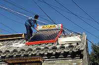 A man installs Solar power powered hot water heater tank on house roof in central Beijing , China..14 Oct 2007