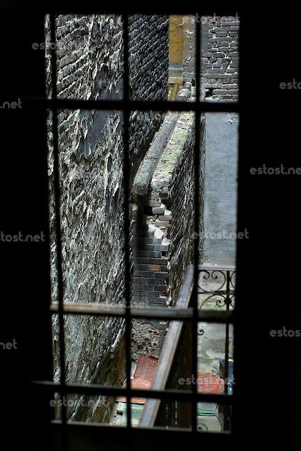 """UNGARN, 04.2009.Budapest - VII. Bezirk .Reste der Ghettomauer (Judenvernichtung 1944/45) im  alten Juedischen Viertel der Elisabethstadt (Erzs?betv?ros):  Blick auf den Hinterhof der Kertesz utca 20 von der Nr.18 aus. Hier wurde der Durchgang zur Wesselenyi utca 37 etc. verschlossen (hinten). Die Ghettogrenze verlief in Budapest nicht entlang von Strassen, sondern wurde hinter den Haeusern ueber Brandwaende und entsprechend verstaerkte Hofmauern gefuehrt, was Aufwand und Sichtbarkeit minimierte..Remains of the Ghetto wall (Holocaust 1944/45) in the old Jewish quarter of the """"Elizabethtown"""" district: View of the backyard of Kertesz street 20 from no. 18. Here the opening to Wesselenyi street 37 etc. was closed (in the rear). The ghetto boundary in Budapest did not follow open streets, but was drawn behind the houses using party walls and reinforced courtyard walls, thus minimizing effort and visibility..© Martin Fej?r/EST&OST"""