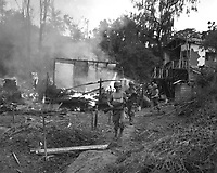 """Leathernecks lead patrol between destroyed buildings in """"mop-up"""" of Wolmi Island, gateway to Inchon.  September 15, 1950.  Sgt. Frank C. Kerr. (Marine Corps)<br /> NARA FILE #:  127-N-A2739<br /> WAR & CONFLICT BOOK #:  1423"""