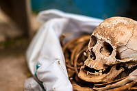 """A dried-up scull and bones are seen wrapped in a cloth and placed in a wooden crate inside a niche at the cemetery in Pomuch, Mexico, 29 October 2019. Every year on the Day of the Dead, people of Pomuch, a small Mayan community in the south of Mexico, visit the cemetery to take part in a pre-Hispanic tradition of cleaning of bones of their departed relatives (""""Limpia de huesos""""). People who die in Pomuch are firstly buried for three years in an above-ground tomb then the dried-up bodies are taken out, bones are separated, wrapped in a decorated cloth, put into a wooden crate, and placed on display among flowers for veneration."""