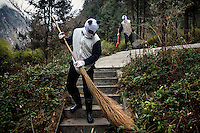 Researchers dressed in panda costumes clean one of the captive born panda enclosures at the Hetaoping Panda Conservation Centre. The researchers wear the panda costumes to prevent the captive born pandas from becoming accustomed to humans.