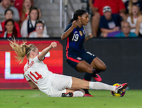 ORLANDO, FL - MARCH 05: Leah Williamson #14 of England slides tackles Crystal Dunn #197 of the United States during a game between England and USWNT at Exploria Stadium on March 05, 2020 in Orlando, Florida.