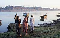 INDIA, Madhya Pradesh, Maheshwar, Holkar fort and temple at Narmada river, villagers cross the river to Maheshwar by boat / INDIEN, Narmada Fluss, Menschen setzen mit einem Boot nach Maheshwar über