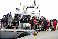 Pictured: Dozens of people disembark the Coastguard vessel that transferred them to safety Thursday 27 November 2014<br />