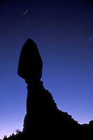 Balanced Rock silhouetted against starry night sky, Arches National Park, Utah.