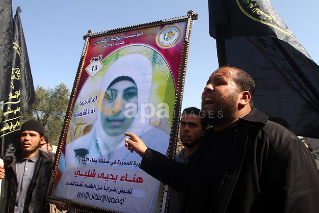 """Palestinian Protestors hold a picture of Palestinian prisoner Hana'a Shalabi during a protest outside the United Nations building in Gaza City on February 28, 2012. Shalabi, released by Israel in a prisoner swap last year but re-arrested earlier this month and held without charge, is on a hunger strike to protest her treatment, officials said. The Arabic writing on the sign reads ''Down with administrative detentions"""".  Photo by Ashraf Amra"""