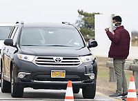 NASSAU, NEW YORK - MARCH 19: Please start to get COVID-19 Test Without Getting out of thier Cars  seen here Guards with masks stop cars at the entrance of Jones Beach as people drive in for coronavirus testing on March 19, 2020 in Nassau, New York. <br /> <br /> <br /> People:  COVID-19