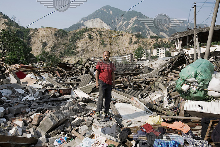 Mr Wu Ze Bing and his wife survived the recent Sichuan earthquake of 12/05/2008, which measured 8.0 on the Richter scale. They are both road construction workers and were up in the mountains when the earthquake struck. They ran back down to their home only to find it destroyed and their nine year old daughter crushed. Their other two sons who are 19 and three years of age were in Dujiangyan, another badly affected city. They have no idea whether they are alive and his wife has gone to the city in search of them. He stands in front of what used to be his home. As the rescue effort goes on the death toll continues to rise, with five million people left homeless in Sichuan.