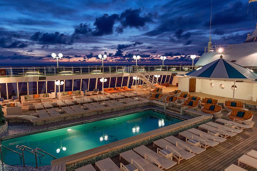 Luxury cruise ship pool at sunset.