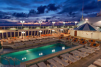 Luxury cruise ship pool at sunset.
