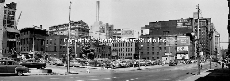 Pittsburgh PA:  View of the point area prior to the Gateway Center construction.  Eppy's parking lot at Liberty Avenue and Fancourt Street in Pittsburgh.  Joseph Horne's store is in the background.  Company signs on city buildings include; Commonwealth Heating Company, M.A. Baskind Company, Demmler and Schenck Company, and Albert L Brahm Company